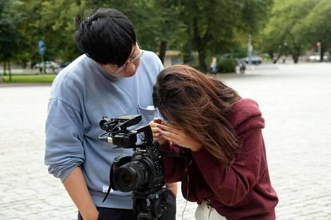 Kuvaaja Jiang Yifeng ja juontaja Irene Liu tutkivat purkitettua materiaalia.