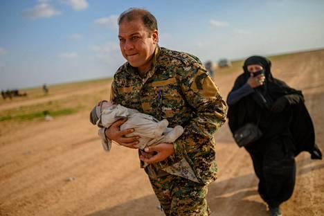 SDF-joukkojen edustaja kantaa vauvaa. Lapsen äiti, joka kulkee perässä, itki ja pyysi apua, AFP kertoo.