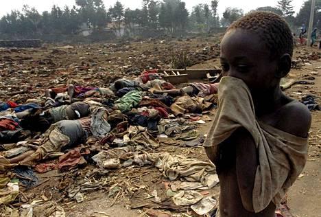 Ruandalainen poika peitti nenänsä paidallaan massiivisen joukkohaudan äärellä heinäkuussa 1994.