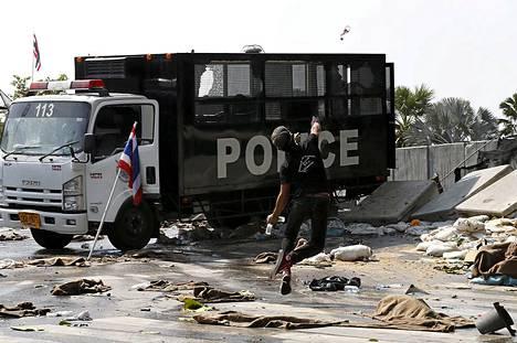 Protestoija heittää poliisiautoa pullolla Bangkokissa.