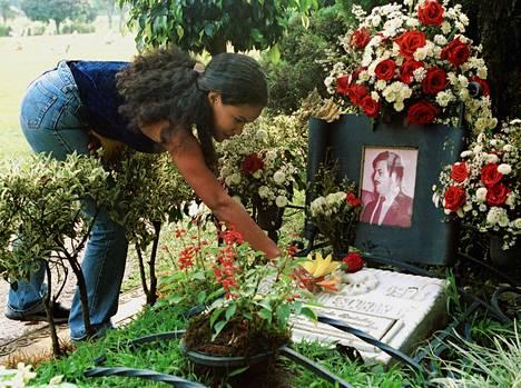 Nainen asettelee kukkia Pablo Escobarin haudalle Medellinin keskushautausmaalla vuonna 2000.