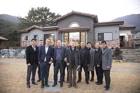 Suomalaiset ja korealaiset herra Shinin talon edustalla. Vasemmalla NamChangin toimitusjohtaja JooYoung Nam, Versowoodin kuusituotteiden vientijohtaja Harri Rantala, toimitusjohtaja Ville Kopra, talon omistaja Yong-Man Shin, myyntijohtaja Eero Valio, toimittaja-metsänomistaja Pasi Jaakkonen, Sang A-timber Ltd:n toimitusjohtaja Man Gil Yu, sekä johtajat Jung Nam Moon, Seung Hyun Lee, Su Yong Lee NamChagnista.