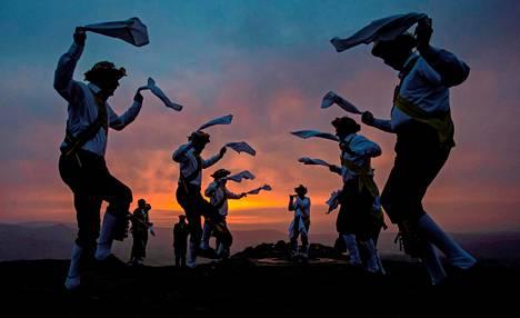 Heippa aurinko!  Tanssiryhmä Chapel-en-le-Frith Morris Dancers otti vastaan auringonnousun muinaiseen kelttiläiseen tapaan vapunpäivänä Britannian Derbyshiressä.