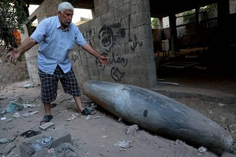 Mies katsoo räjähtämätöntä pommia, jonka israelilaiskone pudotti Gazaan.