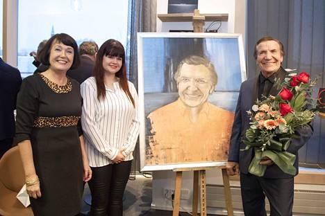 Eino Grön sai 80-vuotislahjaksi muotokuvan ystävättäreltään Anneli Airiolta (vas.). Muotokuvan on maalannut taiteilija Nana Matikkala (kesk.).