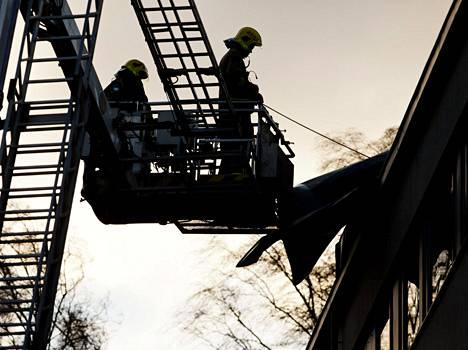 Palomiehet tutkivat myrskyn repimää kattoa tapaninpäivänä Lauttasaaressa, Helsingissä.