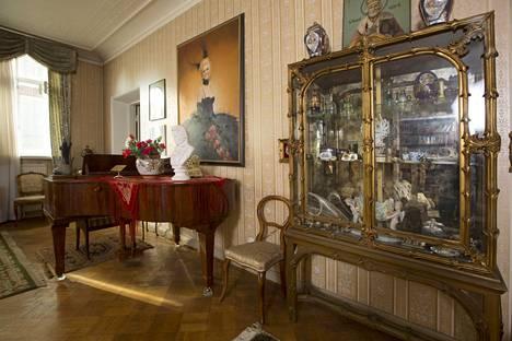 Kodin seinälle on ripustettu muotokuvia talon emännästä. Kuva on Iloinen leski -esityksestä 1970-luvulta, jossa oli mukana myös Tapani Kansa.