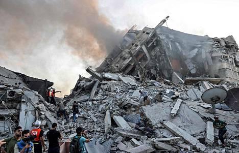 Pelastustyöntekijöitä ja paikallisia al-Sharoukh-tornitalon raunoilla Israelin ilmaiskun jälkeen.
