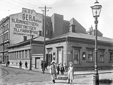 Tytöt kantavat pyykkikoria Yrjönkadun ja Iso Roobertinkadun risteyksessä vuonna 1907.
