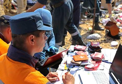 Venäläinen pelastushenkilöstö tutki turmapaikalta löytyneitä passeja.
