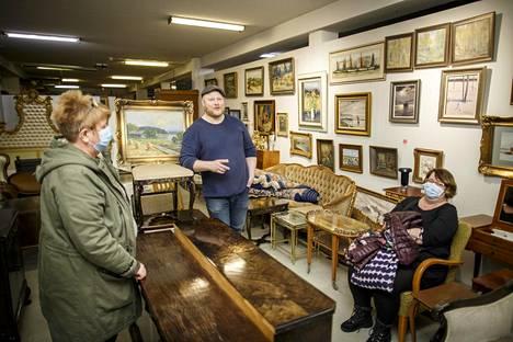 Anne Lindstedt, huutokauppayrittäjä Sami Taustila ja Katri Helander pohtivan Tynellin valaisimen kohtaloa Huutokauppahuone Aleksin tiloissa.