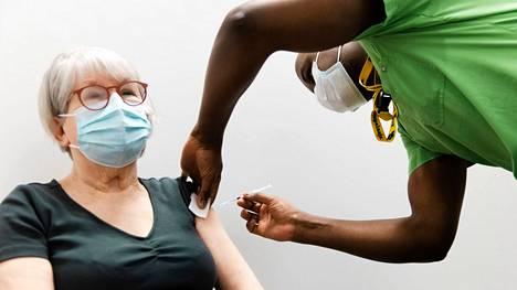 Britanniassa kaikki yli 70-vuotiaat suunnitellaan rokotettavaksi kolmannen kerran. Kuvassa espoolainen Anneli Lundqvist, 76 sai ensimmäisen rokoteannoksen sairaanhoitaja Peter Kipchumbalta viime maaliskuussa Isossa Omenassa.