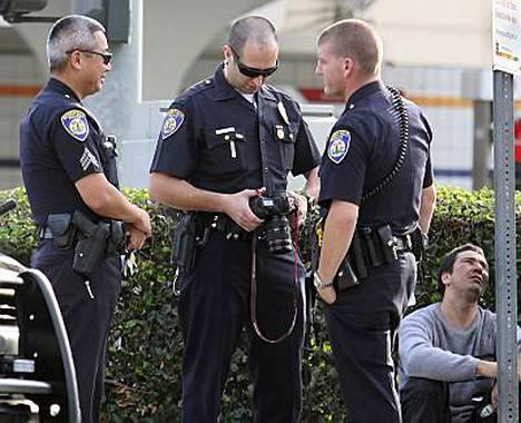 Poliisit tutkivat kameraa, jonka turvamiehet viskasivat valokuvaajan käsistä roskakoriin.