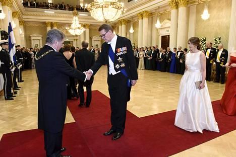Presidentti Sauli Niinistö tervehtii keskustan presidenttiehdokasta Matti Vanhasta ja Heidi Huhtamaata.