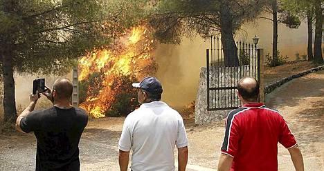 Paikalliset asukkaat hämmästelevät metsäpaloa Valencian alueella.