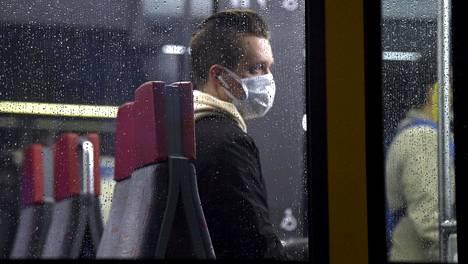 Raitiovaunun matkustaja maski kasvoillaan sateisena syysiltana Helsingissä 8. lokakuuta 2020.