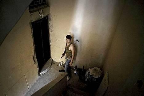 Syyrian kapinallisten taistelija kuvattuna pommitetussa rakennuksessa Aleppossa. Syyriassa tehtiin sunnuntaina Aleppon kaupunkiin ilmaisku, jossa aktivistien mukaan kuoli tai haavoittui kymmeniä ihmisiä.