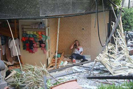 Haavoittunut nainen kuvattiin istumassa tuhoutuneessa talossa.