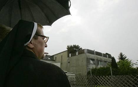 Nunna katseli Itävallan kauhujen taloksi nimettyä rakennusta.