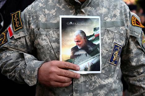Teheranissa perjantaina mielenosoitukseen osallistunut mies kantoi mukanaan Suleimanin kuvaa.
