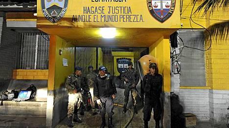 Poliisin ja armeijan edustajat vartioivat vankilan porttia samaan aikaan, kun palomiehet tekivät työtään.