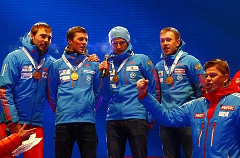 Dmitri Gubernijev (oik.) juhli Venäjän viestijoukkueen kultamitalia vuoden 2017 ampumahiihdon MM-kisojen palkintojenjaossa.