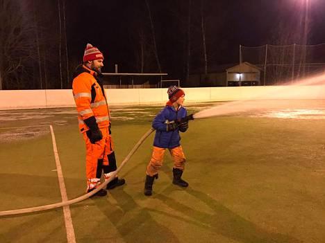 Isä Aatu Johansson tekemässä jäätä poikansa Aimon kanssa.