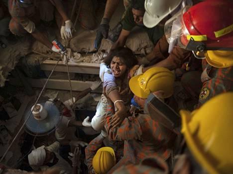 Naista pelastetaan Rana Plazan -vaatetehtaan raunioista.