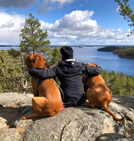 Kaksi koiraa, ihminen ja järvimaisema. Paikkana Hiidenvuori, Iitti.