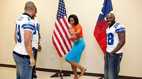 Michelle Obama oppi hyödyntämään julkisuutta taitavasti. Kuvassa hän pallottelee amerikkalaista jalkapalloa pelaavan Dallas Cowboy -joukkueen pelaajien kanssa.