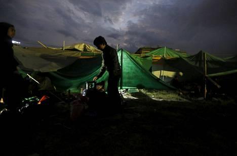 Nepalilaispoika valmistautui valmistamaan illallista Kathmanduun nousseessa telttakylässä.