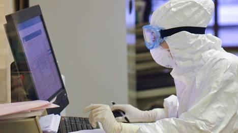 Suojapukuun pukeutunut työntekijä tutkii epäiltyjen koronaviruspotilaiden tietoja Moskovassa Sklifosovskin tutkimusinstituutissa.
