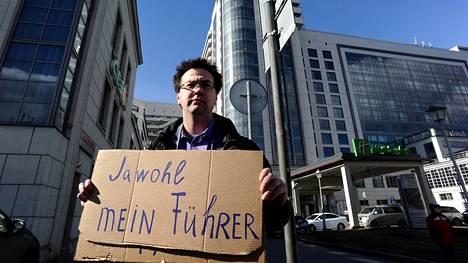 Venäläinen oppositioaktivisti osoitti mieltään kokouspaikan ulkopuolella natsi-Saksaan viittaavan kyltin kanssa.