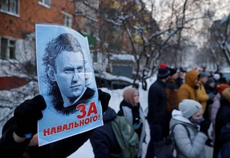 """Yleisöä kerääntyi Himkin poliisitalon edustalle odottamaan tuomion julistamista. Tällä miehellä on kyltissään teksti """"Navalnyin puolesta""""."""