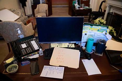 Mielenosoittaja jätti viestin edustajainhuoneen demokraattisen puhemiehen Nancy Pelosin työpöydälle, kun tiloja oli vallattu.