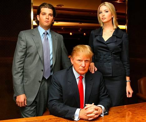 Donald Trump poseeraa lastensa ja työkavereidensa Donald Trump jr:n ja Ivanka Trumpin kanssa kokoushuoneessaan.