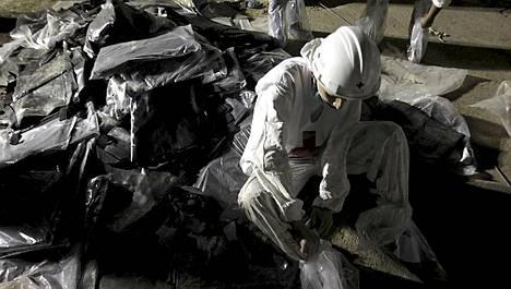Punaisen ristin työntekijä valmistautuu vankila-alueelle menemiseen peittämällä kenkänsä muovipusseilla.