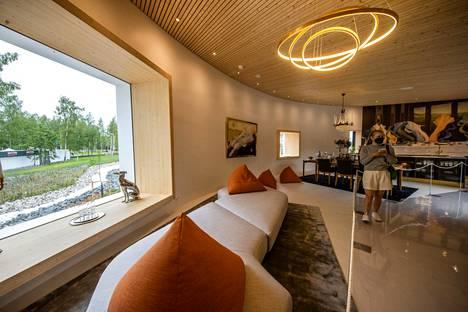 Kaareva olohuone on sisustettu lämpimillä sävyillä.