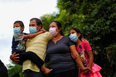 Korona vei. Perhe osallistui koronavirukseen kuolleen sukulaisen hautajaisiin El Salvadorin pääkaupungissa San Salvadorissa maanantaina.