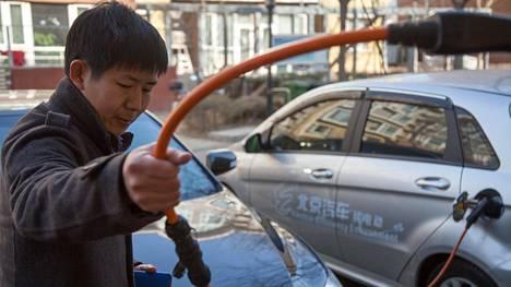 Su Tianjun, 34, lataa kiinalaisvalmisteista BAIC E150 EV -sähköautoaan kotipihallaan Pekingissä.