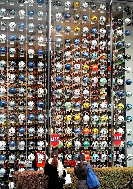 Näyttävä näyteikkuna japanilaiseen tyyliin. Jalkapalloon erikoistuneen urheiluliikkeen näyteikkuna Tokiossa Japanissa. Liike houkuttelee asiakkaita sadoilla jalkapalloilla.
