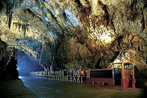 Juna kuljettaa matkalaisia läpiPostojnan jylhän luolaston Sloveniassa.