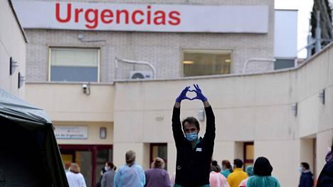 Terveydenhuollon työntekijä muodosti sormillaan sydänkuvion poseeratessaan kameralle Madridissa perjantaina.