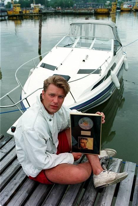 Tauski poseerasi Sinä vain -albumista saamansa kultalevyn kanssa vuonna 1995. Kuvassa huomion kiinnittävät myös Tauskin punaiset minisortsit.