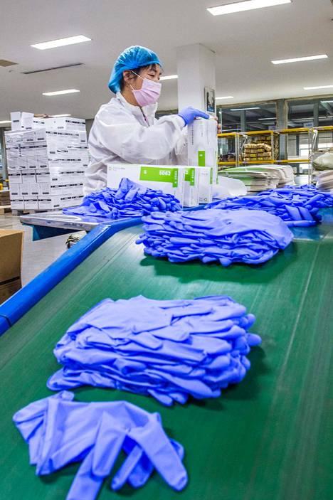 Kertakäyttökäsineitä valmistavan tehtaan tuotantoa kuvattuna tiistaina Kiinan Shandongissa.