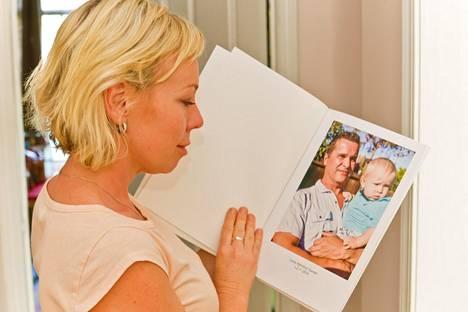 Kristina Duff katselee kuvaa, jossa avomies Jyrki Suutari pitelee pariskunnan Lucas-poikaa sylissään.
