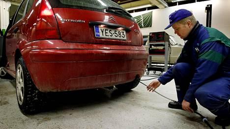 Katsastusmies Jarmo Asikainen asetti mitta-anturria bensiiniauton pakoputkeen.