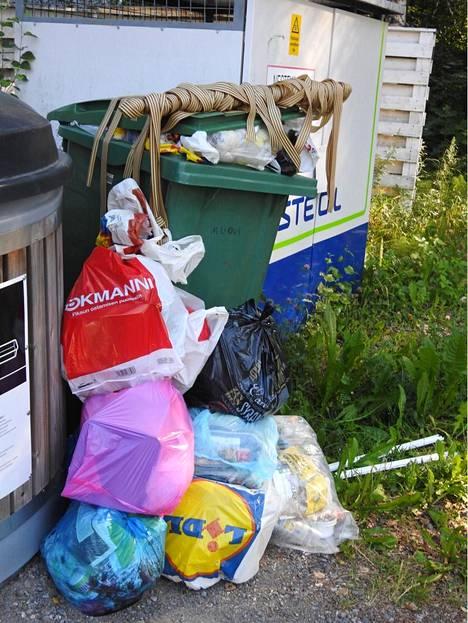 Täysien jäteastioiden viereen kertyy lisää haisevia jätteitä.