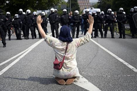 Nainen mielenosoituksessa torstaina. Monessa mielenosoituksessa osallistujat ovat istuneet maassa protestin merkiksi.