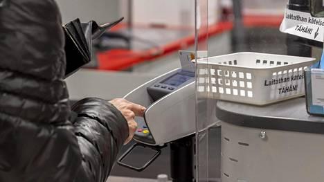 Kassatyöntekijä toivoo, että ruokakaupassa käyvät asiakkaat toimisivat kuten kuvassa ja maksaisivat kortilla, eivät käteisellä. Kuvituskuva.
